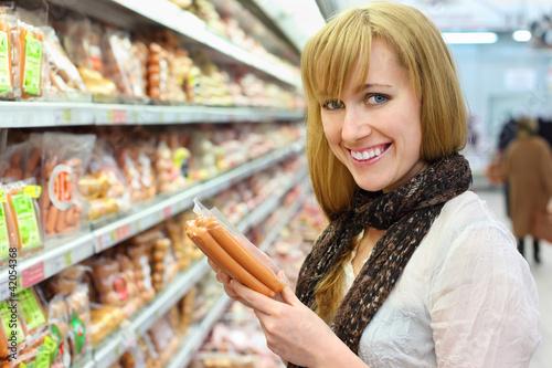 Fotografia Happy blonde girl wearing white shirt chooses sausage