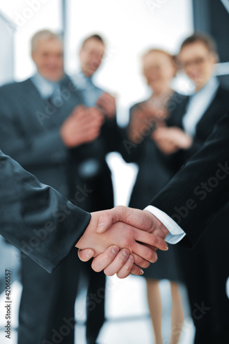 Photo Succesful handshake with business people aplauding