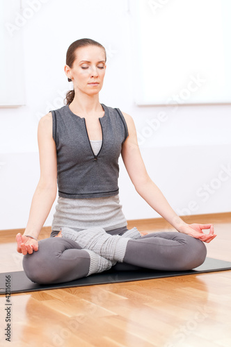 Fotobehang School de yoga Woman doing stretching yoga exercise at sport gym