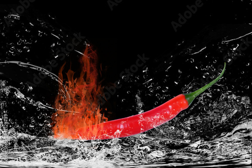 Fotografie, Obraz  Brennende Chilischote mit Wasserspritzern