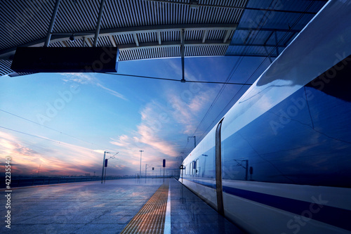 Poster  train stop at railway station with sunset