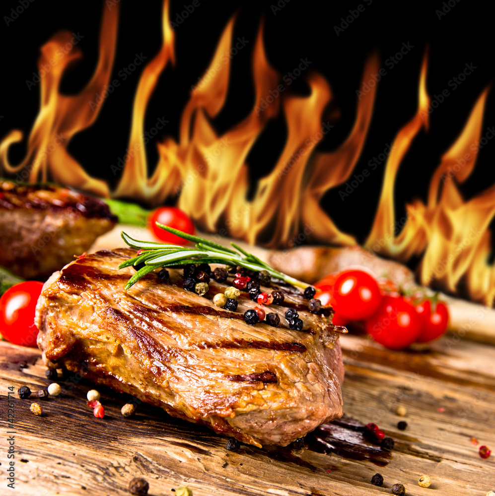 Fototapeta Grilled beef steaks with flames on background