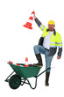 Traffic worker with cone and wheelbarrow