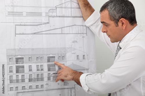 Valokuva  Architect examining a blueprint in detail