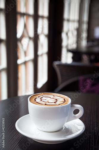 Fototapeta mocha coffee drink on a wood table by the window obraz na płótnie