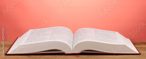 Open book on wooden table on red background Canvas Print