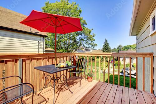 Fototapeta Deck with red umbrella with warm wood. obraz na płótnie