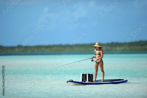 Deurstickers Vissen Woman in bikini fishing and paddle boarding