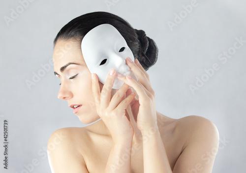 Młoda kobieta trzymająca maskę obok twarzy - fototapety na wymiar