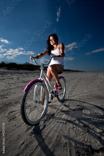 Fototapeta Young Brunette Woman riding bike on Beach obraz na płótnie