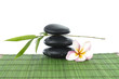 Zen stones and frangipani and a bamboo leaf on green mat