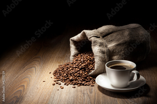 Coffee cup with burlap sack of roasted beans on rustic table #42711739
