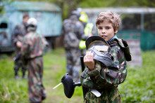Boy In Camouflage Holds Paintb...