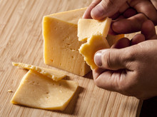 Man Holding Piece Of Cheese