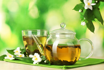 Fototapeta green tea with jasmine in cup and teapot