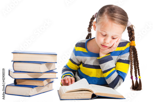 Fotografie, Obraz  schoolgirl  attentively reading the book on isolated white