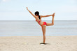 Athletic young woman is training exercises on the beach.