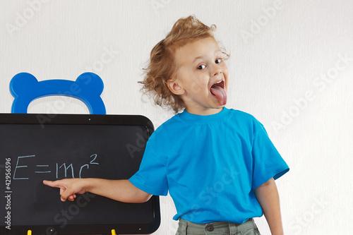 фотография  Little boy shows tongue like Einstein near formula