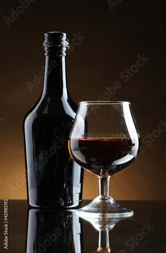 Spoed Foto op Canvas Bar Glass of brandy and bottle on brown background