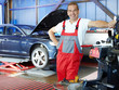 Motor mechanic in a garage is fitting winter tires