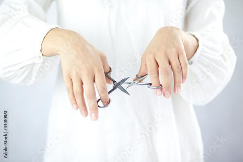 Kobieta trzymająca w dłoniach nożyczki do paznokci