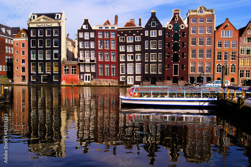 In de dag Amsterdam Traditional houses of Amsterdam with canal reflections