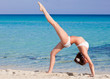 Woman is doing flexibility exercise on the beach