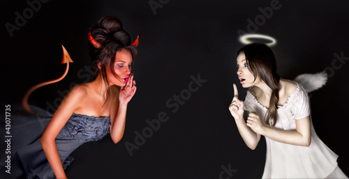 Fotografia Portrait of angel and devil girls and copyspace between them.