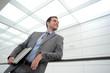 Businessman in grey suit standing in hallway