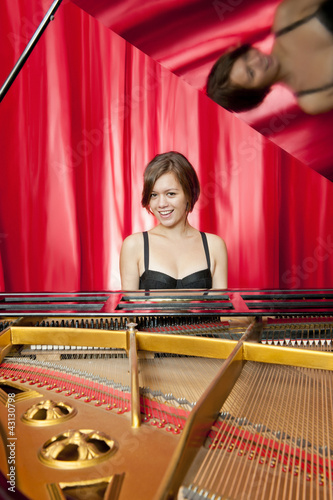 Canvas Print Pretty young woman playing a grand piano