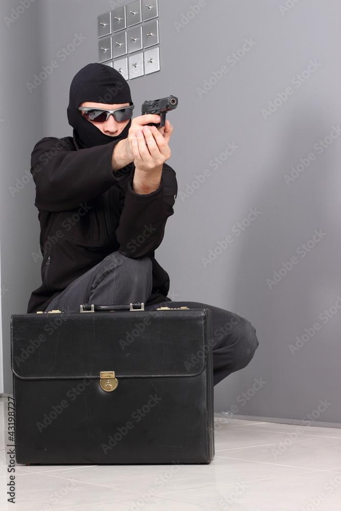 Fototapeta Burglar steals a suitcase full of money.