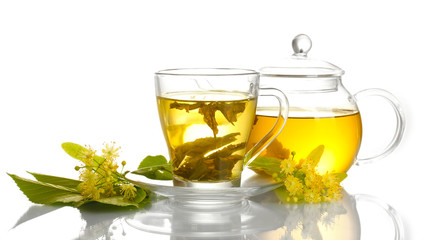 Fototapetacup and teapot of linden tea and flowers isolated on white