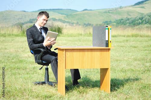 Foto  Geschäftsmann am Schreibtisch draußen