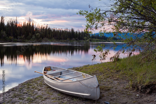 Fotografija Sunset sky and canoe at Teslin River Yukon Canada