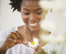 Black Woman Plucking Petals From Daisy