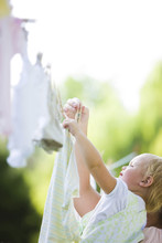 Caucasian Mother And Baby Hanging Laundry On Clothes Line