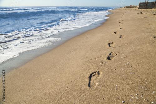 Foto-Leinwand - Orme di un uomo che passeggia sulla spiaggia in riva al mare (von zoomonpictures.it)