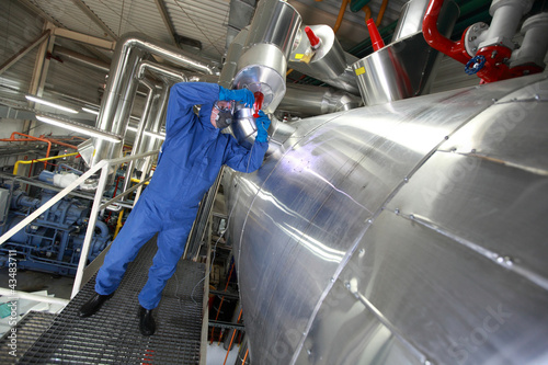 Photo Technician in  blue uniform reparing technological system