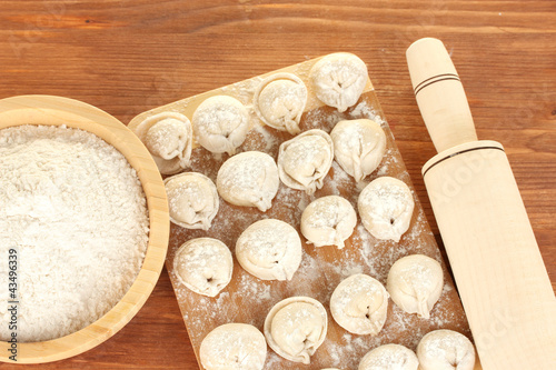 Printed kitchen splashbacks Dairy products Raw Dumplings on cutting board on wooden background close-up