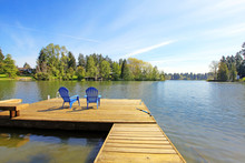 Lake Waterfront With Pier And Two Blue Chairs.