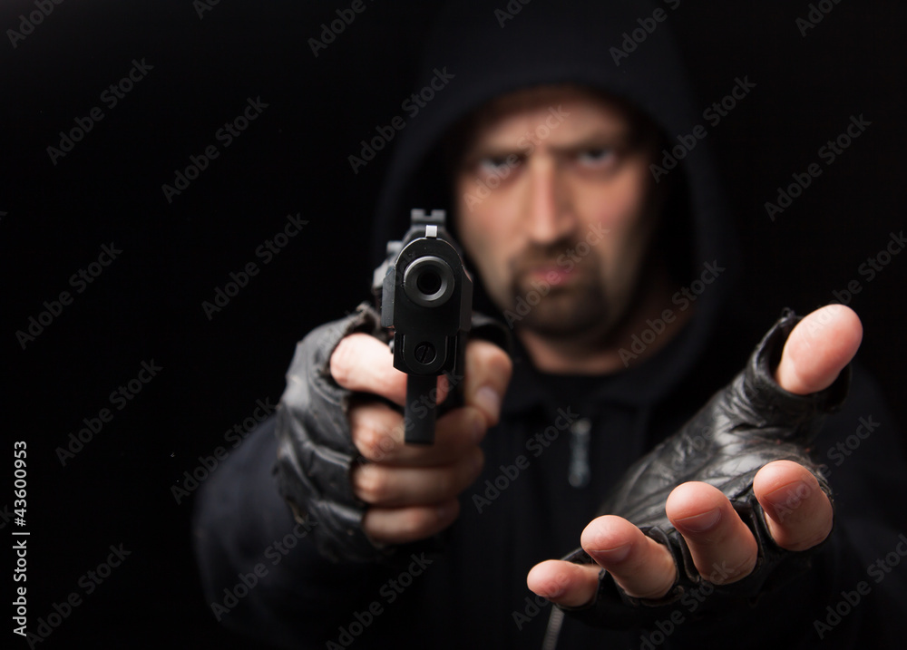 Fototapeta Robber with gun holding out hand