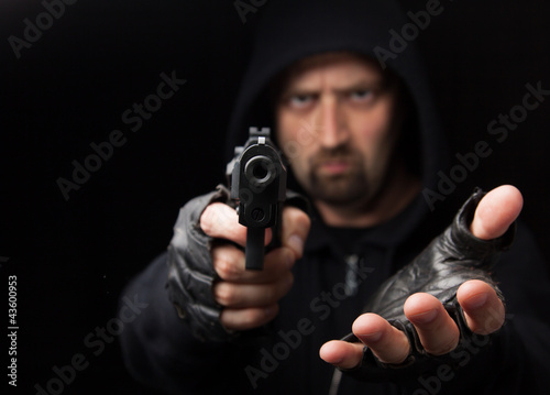 Fotografía Robber with gun holding out hand