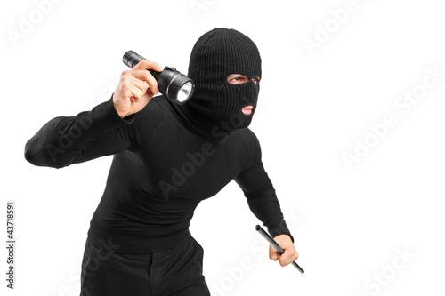 Fotografia A thief holding a flashlight and piece of pipe