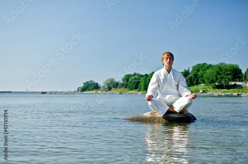 Garden Poster Martial arts Man in kimono meditating on the rock in the sea