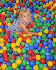 Fototapeta na wymiar Happy girl playing in balls.
