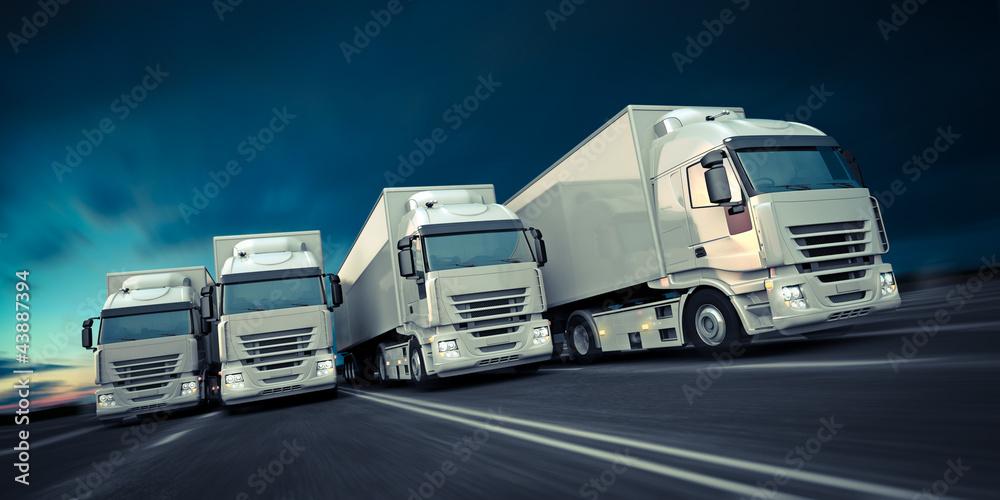 Eine Gruppe LKW fährt schnell auf einer Straße