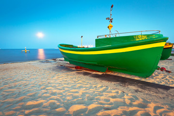 Obraz na Szkle Green fishing boat on the beach of Baltic sea, Poland