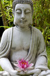 Buddha sculpture with lotus and bamboo leaves in background