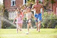 Family Running Through Garden Sprinkler