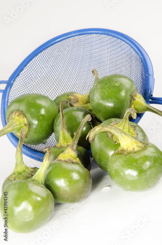 green cherry peppers and a small blue sieve after cleaning